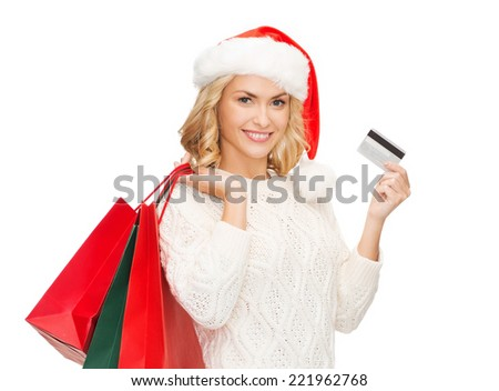 sale, gifts, christmas, xmas concept - smiling woman in santa helper hat with shopping bags and credit card - stock photo