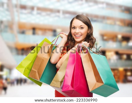 sale, gifts, holidays and people concept - smiling woman with colorful bags over shopping center background - stock photo