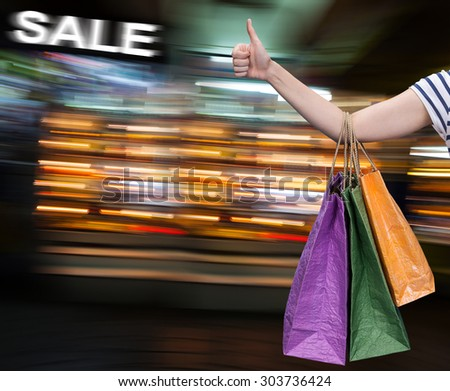 Sale. Hand with shopping bags against blurred mall on the background with copy-space - stock photo