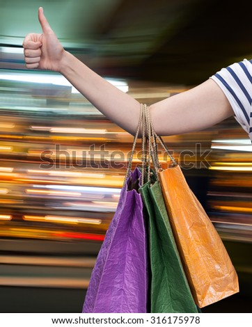 Sale. Hand with shopping bags against blurred mall on the background with copy-space