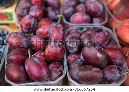 sale, harvest, food, fruits and agriculture concept - close up of satsuma plums in plastic boxes at street market - stock photo