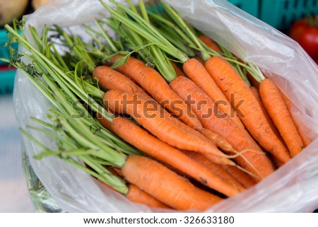 sale, harvest, food, vegetables and agriculture concept - close up of carrot in plastic bag at street market - stock photo