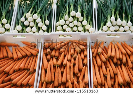 Sale of fresh vegetables in the grocery store. Carrot and onion - stock photo