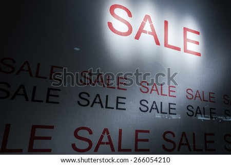 sale poster light up in fashion shop display window  - stock photo