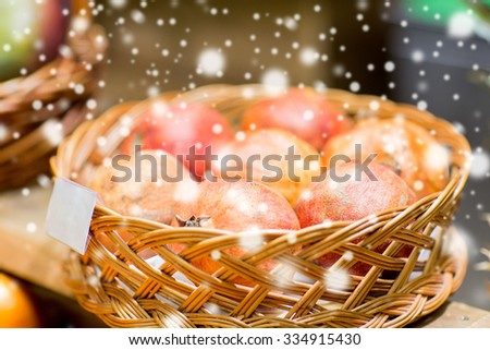sale, shopping and eco food concept - ripe pomegranates in basket with nameplate at grocery store or market over snow effect - stock photo