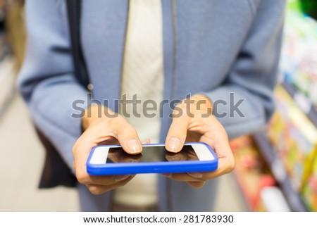 sale, shopping, consumerism and people concept - close up of woman with smartphone choosing and buying food in market - stock photo