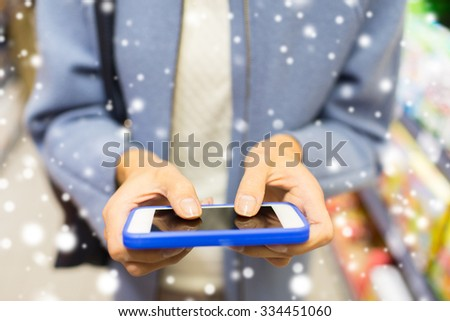 sale, shopping, consumerism and people concept - close up of woman with smartphone choosing and buying food in market over snow effect - stock photo