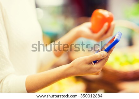 sale, shopping, consumerism and people concept - close up of young woman hands with smartphone and persimmon in market - stock photo