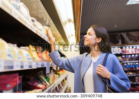 sale, shopping, consumerism and people concept - happy young woman choosing and buying food in market - stock photo
