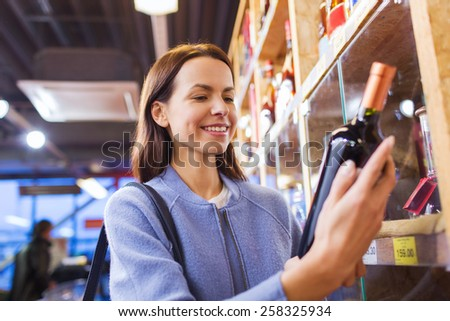 sale, shopping, consumerism and people concept - happy young woman choosing and buying wine in market - stock photo