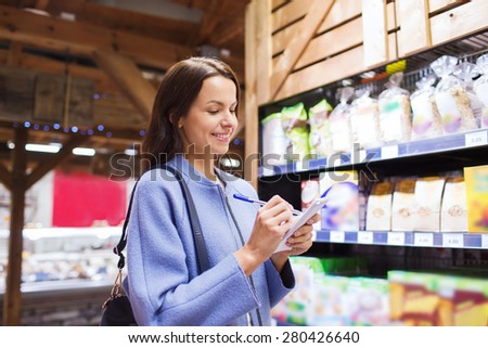 sale, shopping, consumerism and people concept - happy young woman taking notes to notebook in market - stock photo