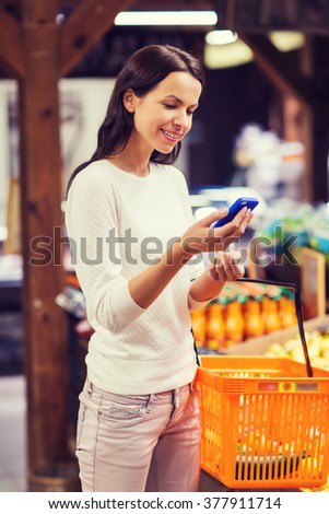 sale, shopping, consumerism and people concept - happy young woman with food basket and smartphone in market - stock photo