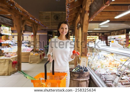 sale, shopping, consumerism and people concept - happy young woman with food basket and tomatoes in market - stock photo