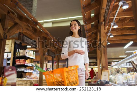 sale, shopping, consumerism and people concept - happy young woman with food basket in market - stock photo