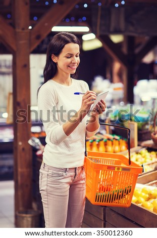 sale, shopping, consumerism and people concept - happy young woman with food basket taking notes to notebook in market