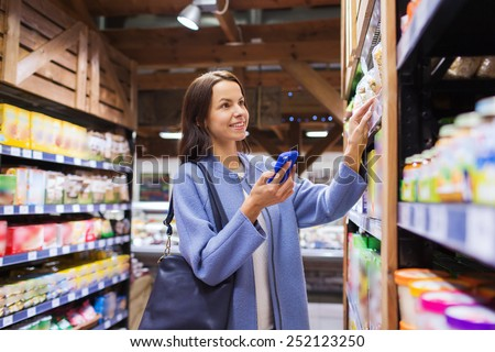 sale, shopping, consumerism and people concept - happy young woman with smartphone choosing and buying food in market - stock photo