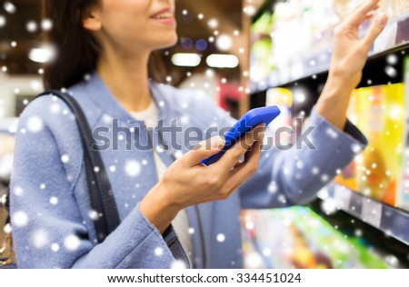 sale, shopping, consumerism and people concept - happy young woman with smartphone choosing and buying food in market over snow effect - stock photo