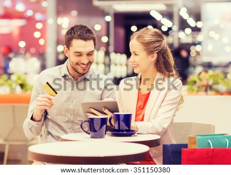 sale, shopping, consumerism, leisure and people concept - happy couple with tablet pc and credit card drinking coffee in mall - stock photo
