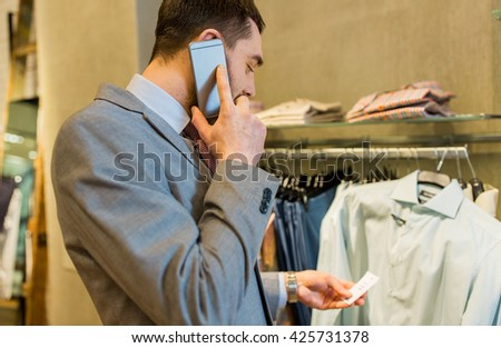 sale, shopping, fashion, communication and people concept - close up of young man calling on smartphone and looking to shirt price tag at clothing store - stock photo