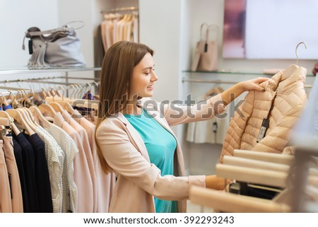 sale, shopping, fashion, style and people concept - happy young woman choosing clothes in mall or clothing store