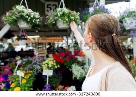 sale, shopping, gardening and people concept - close up of woman choosing flowers at street market