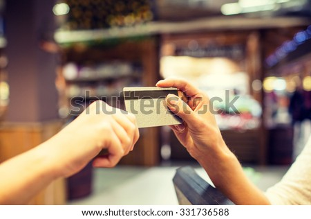sale, shopping, payment, consumerism and people concept - close up of hands giving credit card at checkout in market or mall - stock photo