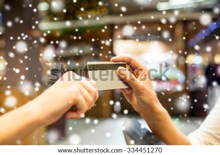 sale, shopping, payment, consumerism and people concept - close up of hands giving credit card at checkout in market or mall over snow effect - stock photo