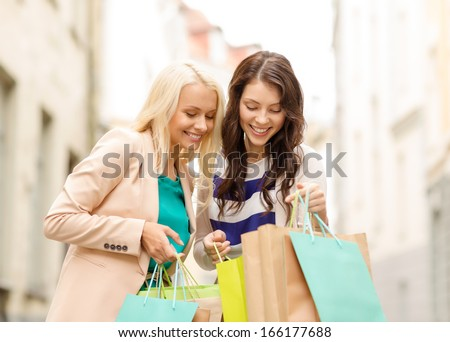 sale, shopping, tourism and happy people concept - two beautiful women looking inside shopping bags in the ctiy - stock photo