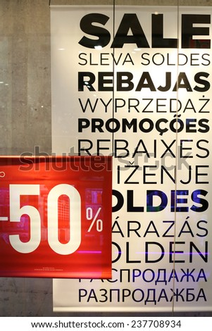 Sale sign in a clothing store window, Sale sign on different languages in the window shop - shopping discount concept  - stock photo
