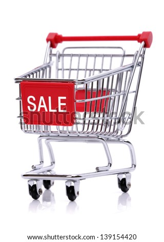Sale sign on red shopping trolley isolated on white background - stock photo