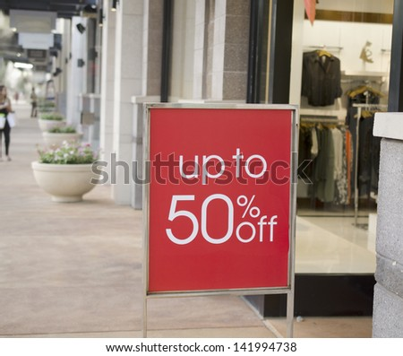 Sale sign outside fashion retail store in shopping mall - stock photo