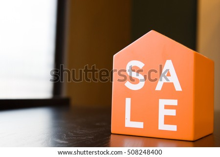 Sale tag on mini home model in orange color