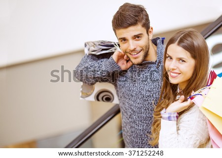 Sale, technology and people concept - happy young couple with shopping bags - stock photo