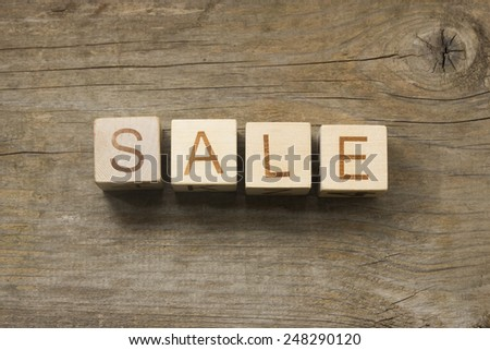 Sale text on a wooden background - stock photo