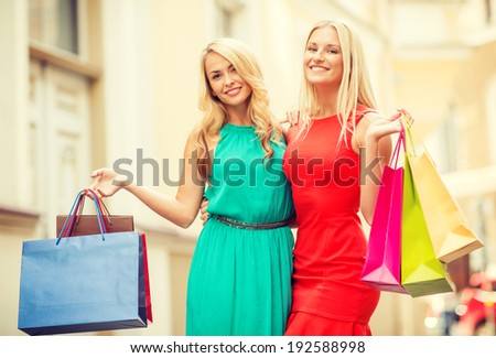 sale, tourism, shopping and happy people concept - two beautiful women with shopping bags in the ctiy - stock photo