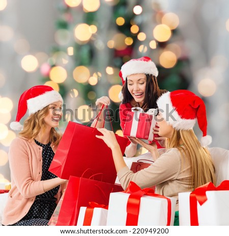 sale, winter holidays and people concept - smiling young woman in santa helper hat with gifts and shopping bags over christmas tree lights background - stock photo