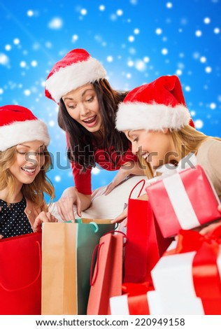 sale, winter holidays, christmas and people concept - smiling young woman in santa helper hat with gifts and shopping bags over blue snowing background - stock photo