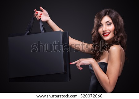Sale. Young smiling woman showing shopping bag in black friday holiday. Girl on dark background with copy space