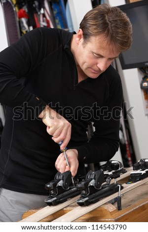 Sales Assistant Adjusting Fittings On Skis In Hire Shop - stock photo