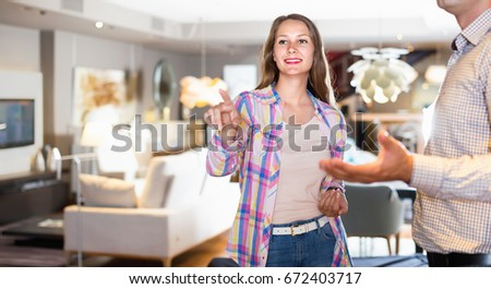 Sales assistant helping smiling positive girl choose new sofa for apartment