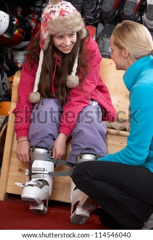 Sales Assistant Helping Teenage Girl To Try On Ski Boots In Hire Shop - stock photo