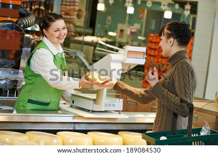 Sales assistant in supermarket demonstrating food cheese to female customer during shopping at store - stock photo