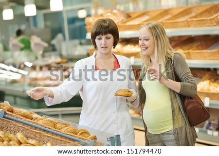 Sales assistant in supermarket demonstrating food to female customer during shopping at store - stock photo