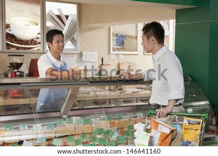 Sales Clerk assisting man at the Deli counter, Beijing - stock photo