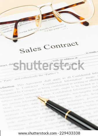 Sales contract document with glasses and pen - stock photo