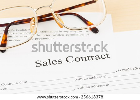 Sales contract document with glasses; document is mock-up - stock photo