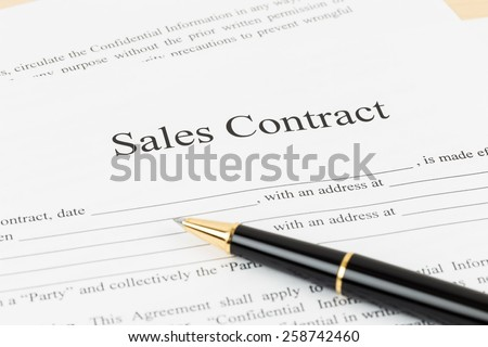 Sales contract document with pen, document is mock-up