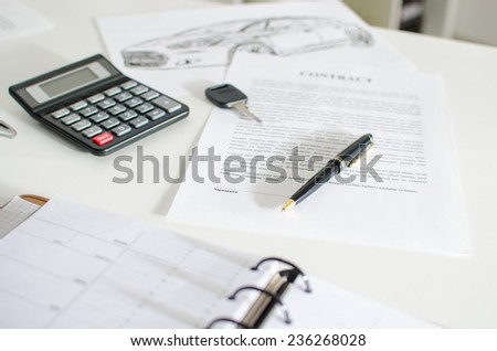 Sales contract, key, pen and calculator on a desk - stock photo