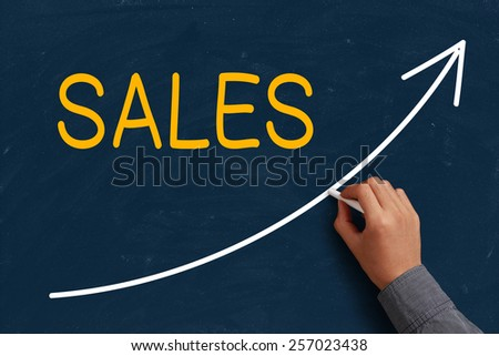 Sales Growth on blue chalkboard with the hand of businessman. - stock photo