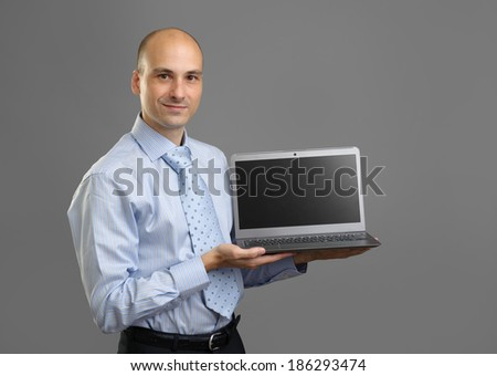 Sales man presenting laptop over gray background - stock photo
